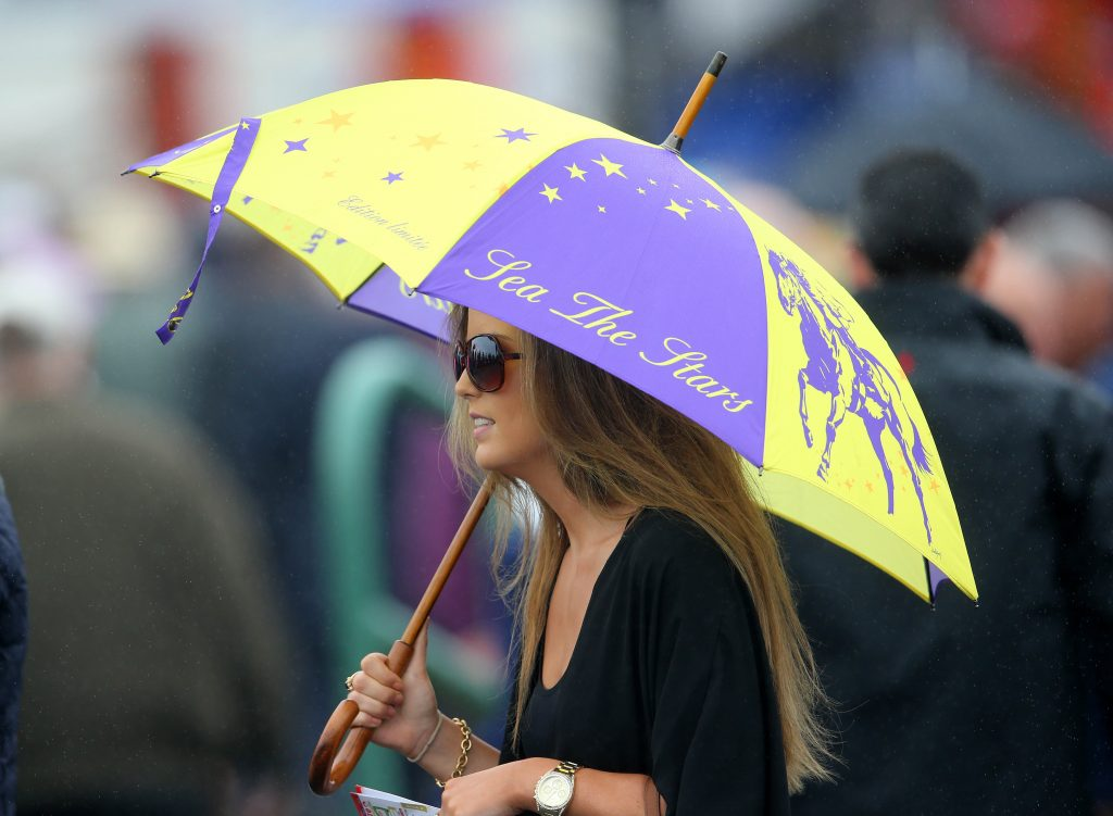 2014 Galway Racing Festival 30/7/2014 Punters shelter from the rain at Ballybrit today Mandatory Credit ©INPHO/Cathal Noonan