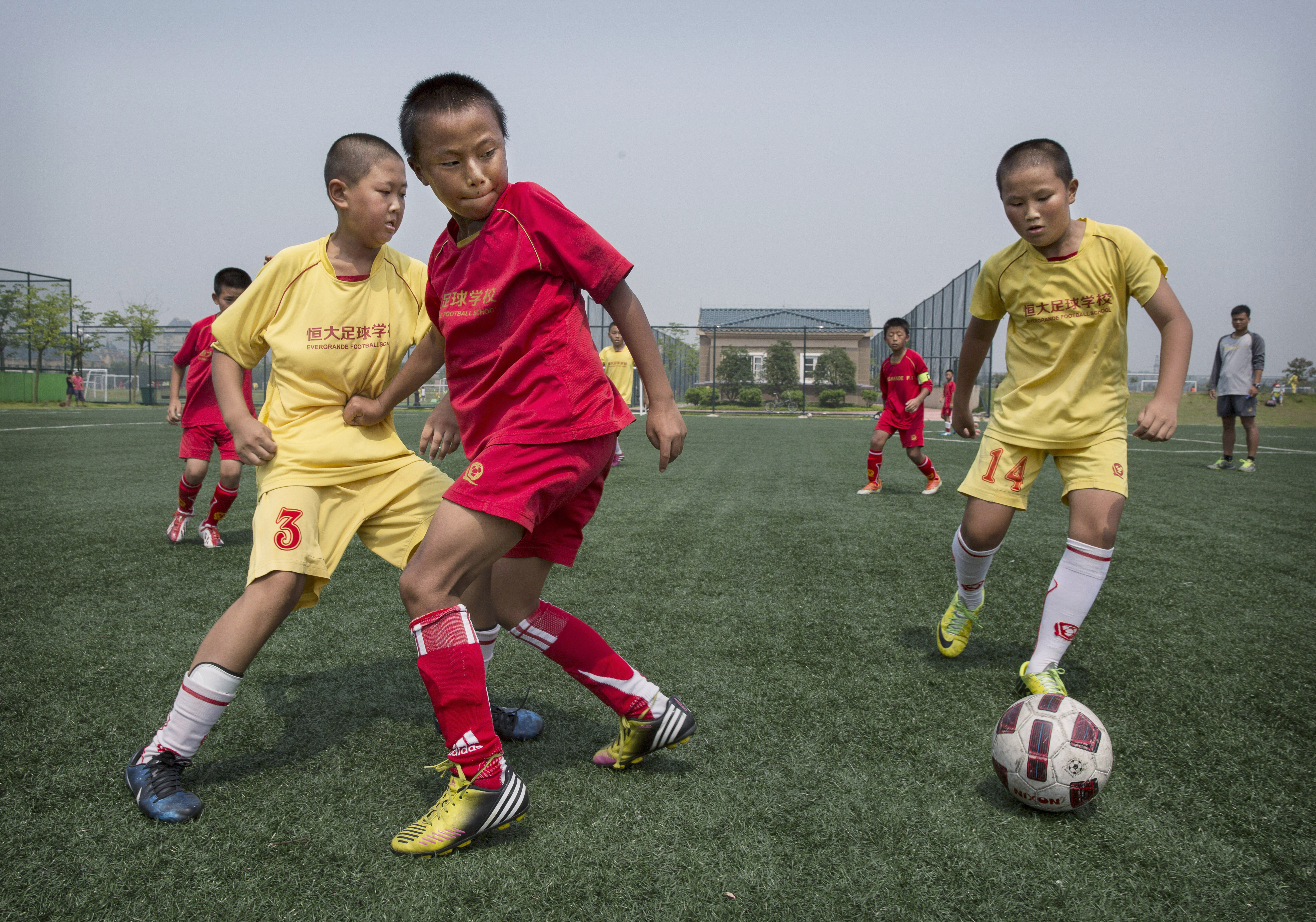 QINGYUAN, CHINA - JUNE 14: Young Chinese students play during a match on a practice pitch at the Evergrande International Football School on June 14, 2014 near Qingyuan in Guangdong Province, China. The sprawling 167-acre campus is the brainchild of property tycoon Xu Jiayin, whose ambition is to train a generation of young athletes to establish China as a football powerhouse. The school is considered the largest football academy in the world with 2400 students, more than 50 pitches and a squad of Spanish coaches through a partnership with Real Madrid. (Photo by Kevin Frayer/Getty Images)